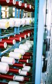 red and white colored yarn spools being used to weave cloth at a textile plant poster
