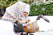 Cute little beautiful baby girl sitting in the pram or stroller on cold day with sleet, rain and snow. Happy smiling child in warm clothes, fashion stylish baby coat. Baby with big umbrella. poster