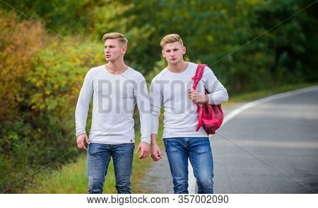 Means Of Travel. Twins Walking Along Road. Two Brothers Go Adventure. Friendship. Men Hitch Hiking.