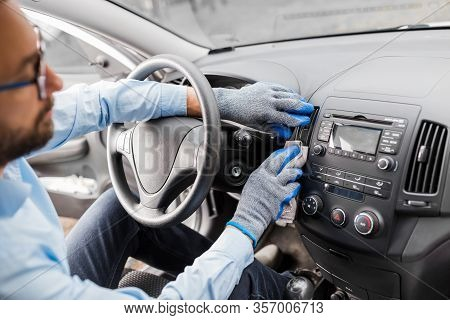 Car Wash Worker Maintaining And Detailing Car Interior Console Shine By Using Microfiber Cloth. Clea