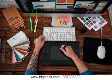 Top View Of A Graphic Designer Using Graphic Tablet And Computer In The Office Or Studio. Workplace