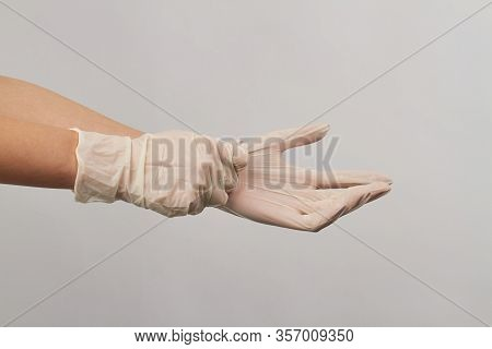 Putting On Disposable Sterile White Gloves On White Background. Close Up Surgical Gloves.