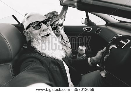 Happy senior couple taking selfie on new convertible car - Mature people having fun together during road trip vacation - Elderly lifestyle and travel transportation concept - Black and white editing
