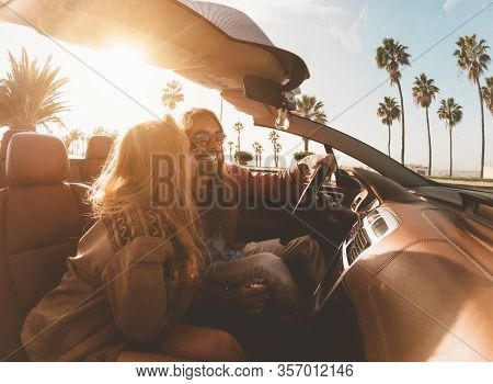 Happy Young Couple Doing Road Trip In Tropical City - Travel People Having Fun Driving In Trendy Con