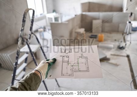 The Construction Worker Hold In Hands Architectural Blueprints. Repair Or Construction Of A New Apar