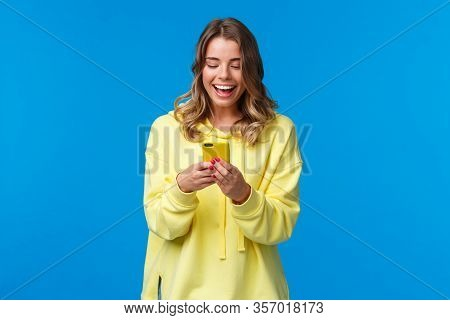 Technology And People Concept. Happy Smiling Blond Girl Using Mobile Phone In Yellow Case, Messaging