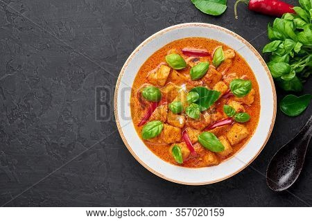 Thai Panang Chicken Curry In White Plate At Black Slate Background. Phanaeng Curry Is Thai Cuisine D