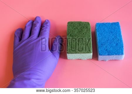 Gloved Hand With Washcloth On Pink Background. Rubber Gloves And A Washcloth For Cleaning On A Pink