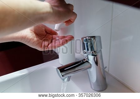 A Woman Uses Anti Bacterial Rinsing Soap To Clean Her Hands To Prevent The Spread Of Virusses And Ba