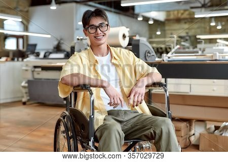 Portrait Of Young Male Office Worker In A Wheelchair Looking At Camera While Posing In Co-working Sp
