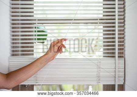 Cropped View Hand Of Woman Pull Rope, Opened Modern White Blackout On Windows, Standing In Light Roo