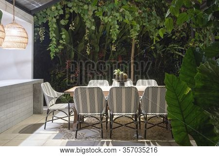 Dining Room Table And Comfortable Chairs On Open Kitchen At Evening Against Green Natural Background