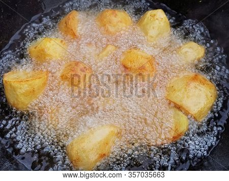 Whole Potatoes Are Fried In A Deep Black Cauldron With A Lot Of Oil . Unhealthy Lifestyle Diet, Fat