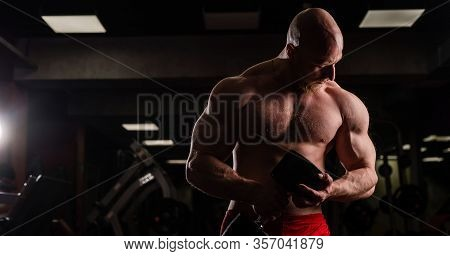 Shirtless Handsome Man Doing Biceps And Chest Exercise With Dumbbell. Macho Guy Bodybuilder. Muscula