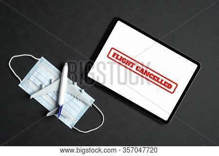 Coronavirus Flight Cancellations Concept. Top View Airplane Toy, Digital Tablet With Message