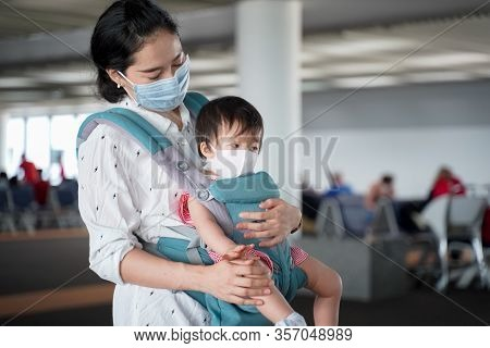 Asian Baby With Mother,baby Travel In Baby Carry In Terminal Area,baby Wearing A Protection Mask Aga