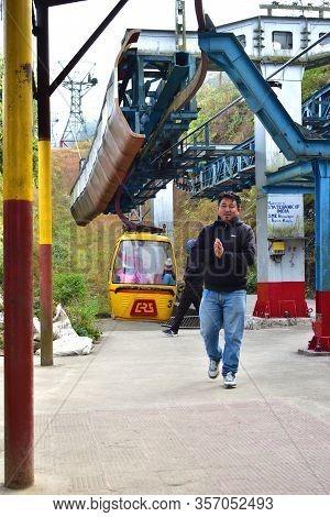 Darjeeling, India- December 27, 2019: Tourists Enjoy A Ropeway Cable Car Or Gondola Ride Over Darjee
