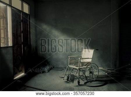 An Old Abandoned Wheelchair In An Old Room