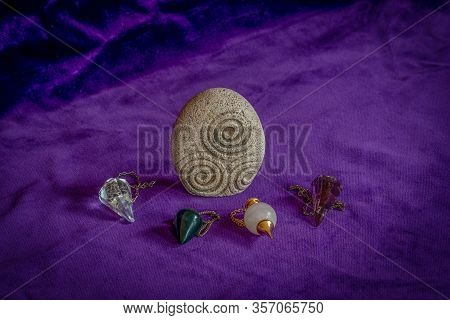 Stone With Triskel Symbol And Four Crystal Dowsing Pedulums On A Purple Velvet Underground