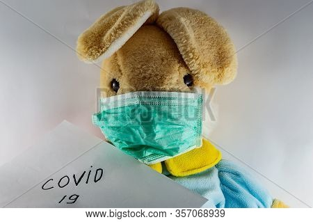 Rabbit In A Protective Medical Mask Lies In A Crib On A White Bed. The Toy Got Sick. Playing Doctor.