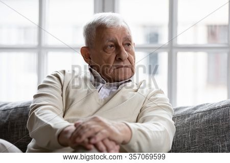 Pensive Old Man Sitting On Couch In Living Room Alone