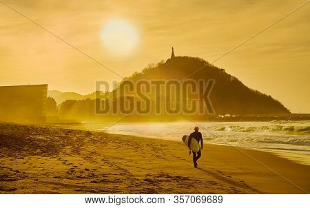 A Surfer Walking On The Zurriola Beach At Sunset With The Monte Urgull In The Background. San Sebast