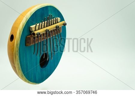 Standing View Of A Blue African Kalimba On A White Background With Space On The Right For Text. Trad