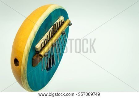 Top View Of A Blue African Kalimba On A White Background With Space On The Right For Text. Tradition