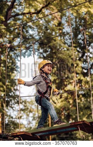 Kid Climbing Trees In Park. Beautiful Little Child Climbing And Having Fun In Adventure Park. Safe C