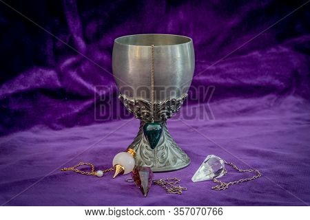 A Tin Goblet And Crystal Dowsing Pedulums On Purple Velvet - Symbol Fortune Telling