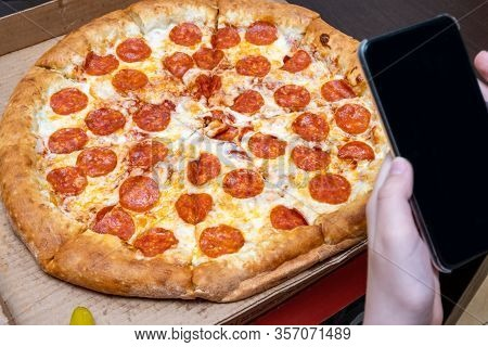 Hands Taking Photos Of Hot Delicious Italian Pepperoni Pizza Using Smartphone.