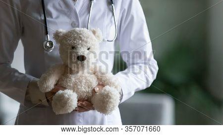 Closeup Female Paediatrician In White Coat Holding Stuffed Toy Bear