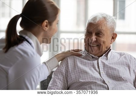 Caring Geriatric Nurse In White Coat Cares For Elderly Man