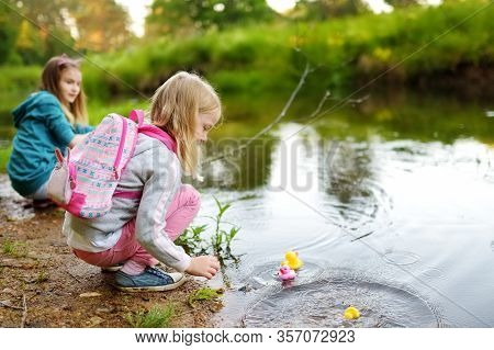 Two Cute Young Sisters Playing By A River With Colorful Rubber Ducks. Children Having Fun With Water