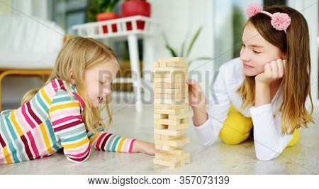 Two Sisters Playing Wood Blocks Tower Game At Home. Kids Practicing Their Physical And Mental Skills