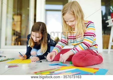 Two Sisters Drawing With Colorful Pencils At Home. Creative Kids Doing Crafts Together. Education An