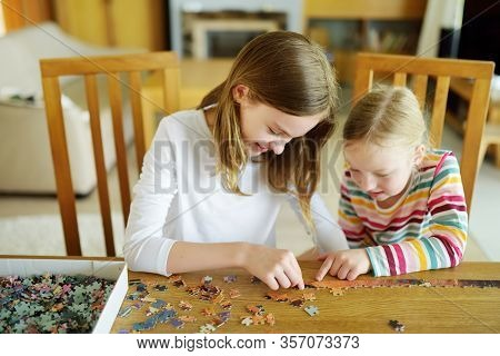 Cute Young Girls Playing Puzzles At Home. Children Connecting Jigsaw Puzzle Pieces In A Living Room