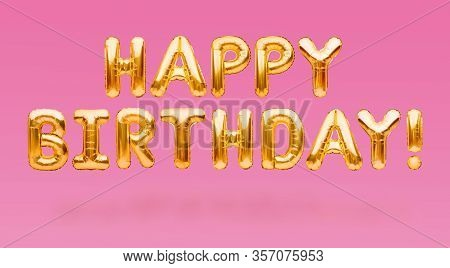 Words Happy Birthday Made Of Golden Inflatable Balloons Floating On Pink Background. Gold Foil Heliu