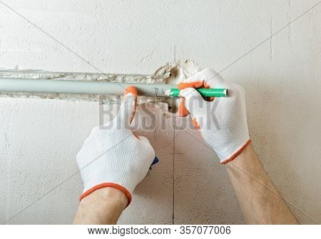 A Worker Is Cutting Off The Part Of The Insulation With A Cutter.