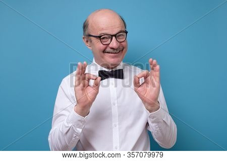 Caucasian Man In White Shirt Smiling On Camera With Alright Ok Sign