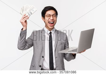 Waist-up Of Excited, Lucky Handsome Rich Asian Guy, Entrepreneur Got His First Money, Selling Or Inv