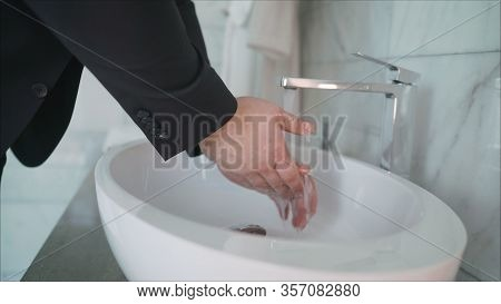 Coronovirus Prevention. A Man Washes His Hands Thoroughly In The Sink. A Man Pours Liquid Soap Into