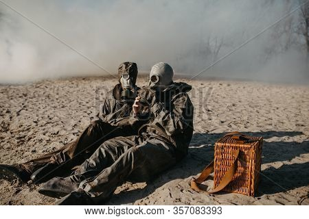 Couple In Love Sits At Outing In Nbc Protective Suits And Gas Masks On Smoke Background. Concept Of