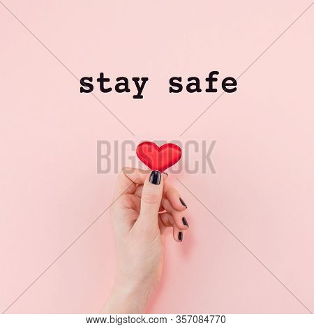 Stay Home, Stay Safe Concept With Red Heart In Hand On Pink Background. Worrying And Caring During C