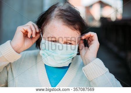 Outdoor Photo Of Elderly Woman Putting Medical Mask On Her Face.
