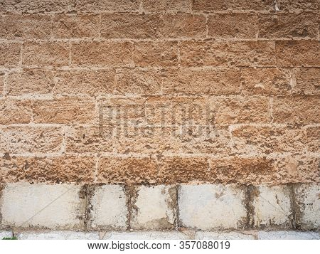 Stony Marble Wall On Base Sandstone Blocks And Pavement, Building Made With Stone Blocks, Against Bl