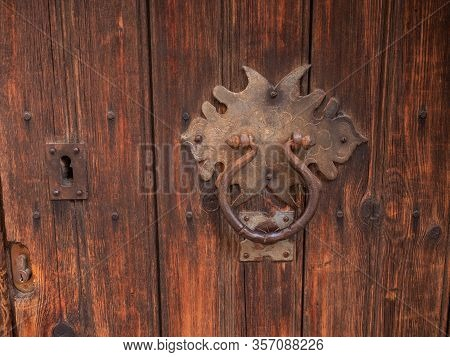Antique Brass Knocker On The Wooden Doors For Knocking. Door Knocker And A Big Vintage Padlock.