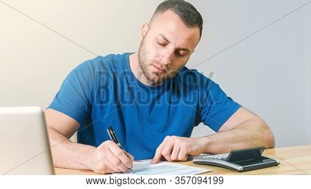 Young Casual Man Filling 1040 Tax Form By Hand With Calculator And Laptop.