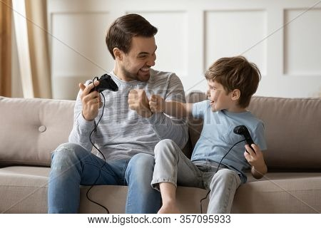 Overjoyed Young Dad And Little Son Play Video Games Together