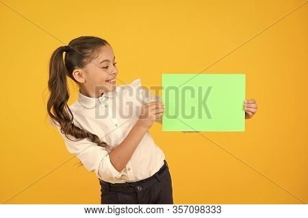 Glorious Colour. Little Girl Holding Empty Sheet Of Paper On Yellow Background. Small Child With Bla